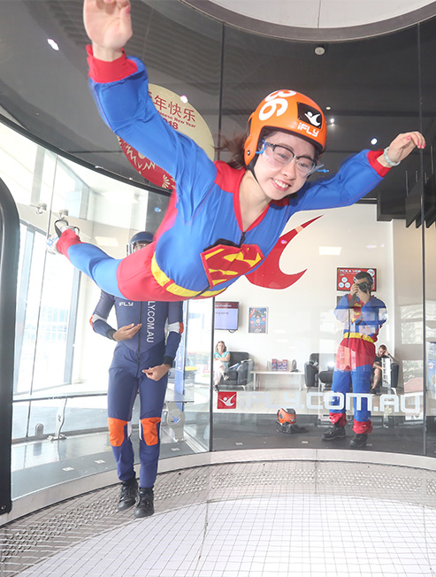 Kid dressed as Superman flying in wind tunnel